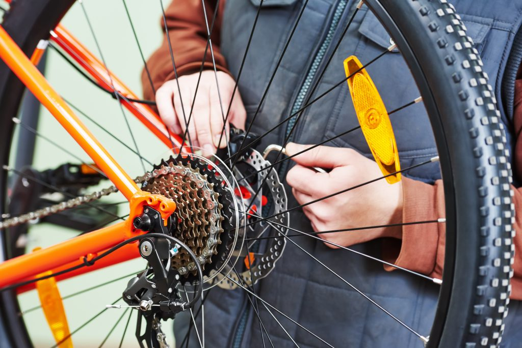 Bike service: mechanic serviceman repairman installing assembling or adjusting bicycle gear on wheel in workshop